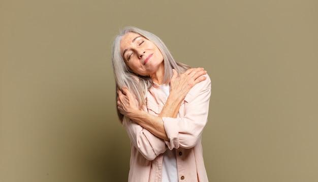Mulher idosa se sentindo apaixonada, sorrindo, se abraçando e se abraçando, permanecendo solteira, sendo egoísta e egocêntrica