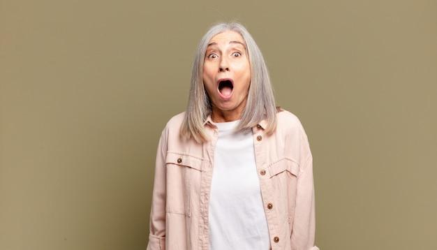Mulher idosa se sentindo apavorada e chocada, com a boca escancarada de surpresa