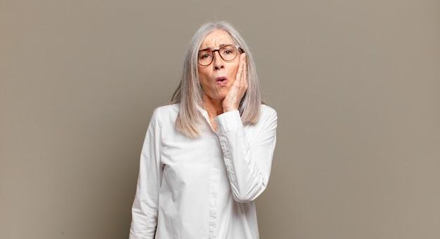 Mulher idosa se sentindo chocada e espantada com a boca aberta, cara a cara, sem acreditar