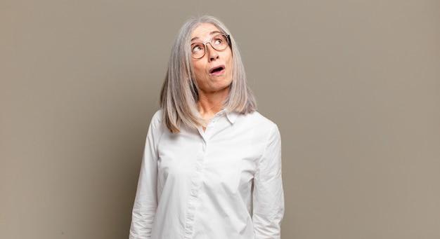 Mulher idosa se sentindo chocada, feliz, maravilhada e surpresa, olhando para o lado com a boca aberta