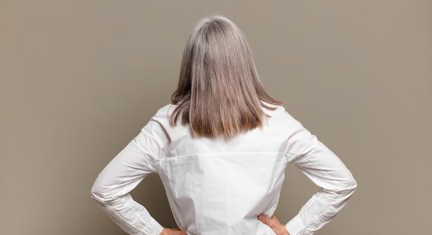 Mulher idosa se sentindo confusa ou cheia ou dúvidas e perguntas, imaginando, com as mãos nos quadris, vista traseira