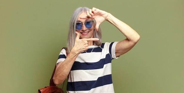 Mulher idosa se sentindo feliz, amigável e positiva, sorrindo e fazendo um retrato