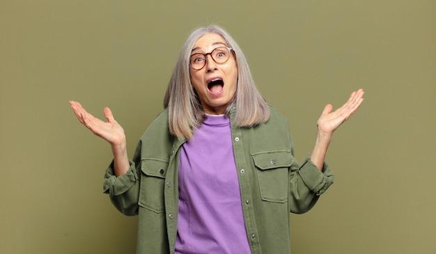 Mulher idosa se sentindo feliz, animada, surpresa ou chocada, sorrindo e atônita com algo inacreditável