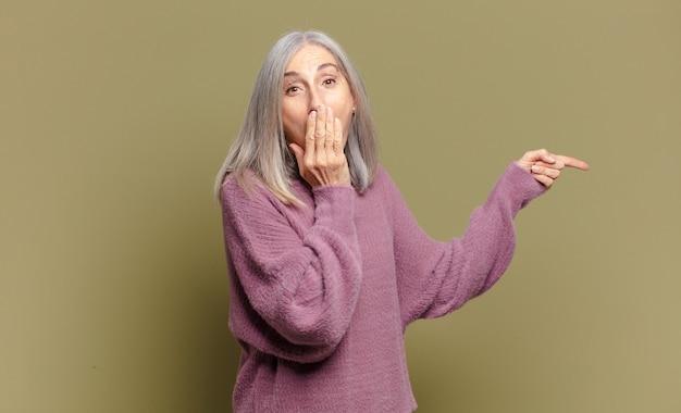 Mulher idosa se sentindo feliz, chocada e surpresa, cobrindo a boca com a mão e apontando para o espaço lateral da cópia