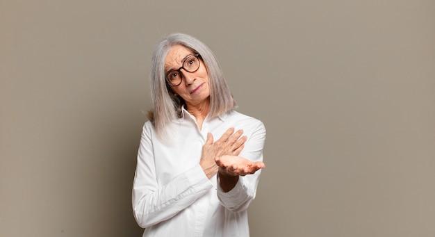 Mulher idosa se sentindo feliz e apaixonada, sorrindo com uma mão próxima ao coração e a outra esticada na frente