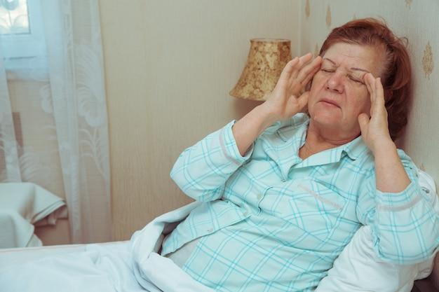 Mulher idosa se sentindo mal na cama, segurando as mãos na cabeça. dor de cabeça pela manhã.