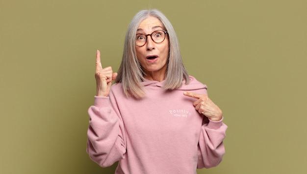Mulher idosa se sentindo orgulhosa e surpresa, apontando para si mesma com confiança, sentindo-se a bem-sucedida número um