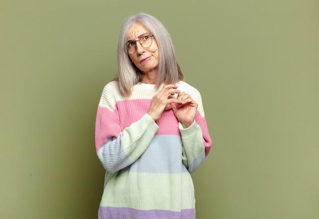 Mulher idosa se sentindo orgulhosa, travessa e arrogante enquanto trama um plano maligno ou pensa em um truque
