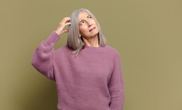 Mulher idosa se sentindo perplexa e confusa, coçando a cabeça e olhando para o lado