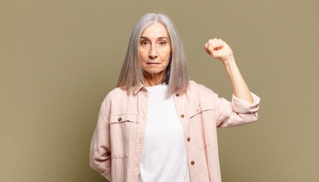 Mulher idosa se sentindo séria, forte e rebelde, levantando o punho, protestando ou lutando pela revolução