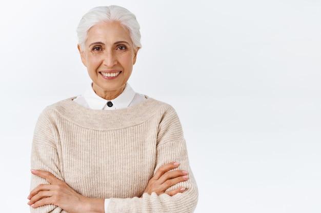Mulher idosa, segura de si, feliz e satisfeita com corte de cabelo grisalho penteado, braços cruzados sobre o peito como um profissional, de pé determinada parede branca