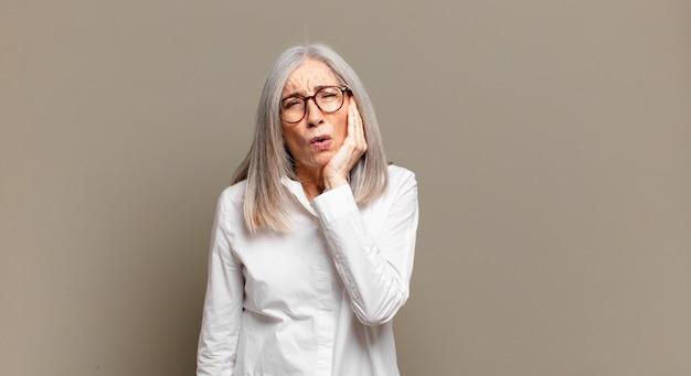 Mulher idosa segurando a bochecha e sofrendo de dor de dente dolorida, sentindo-se doente, infeliz e infeliz, procurando um dentista