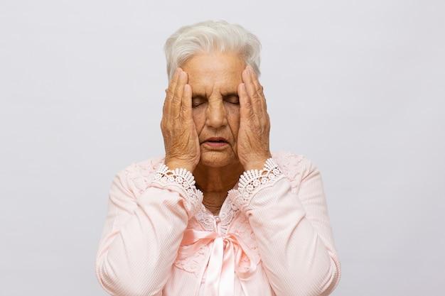 Mulher idosa segurando a cabeça devido a forte dor de cabeça
