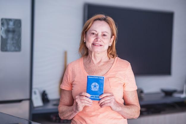 Mulher idosa segurando a carteira de trabalho brasileira na mão. idosa segurando carteira de trabalho brasileira