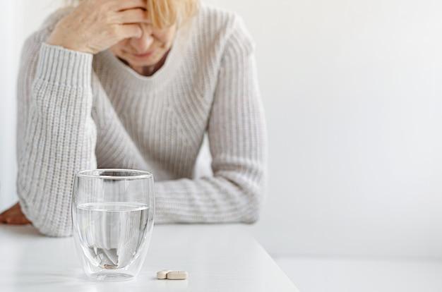Mulher idosa segurando a mão na cabeça dela. foco seletivo em comprimidos e copo de água. conceito de dor de cabeça e estresse