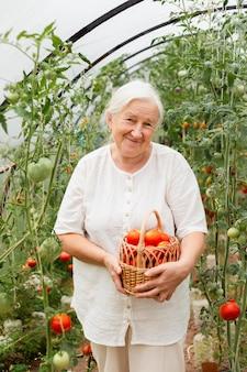 Mulher idosa segurando cesta média