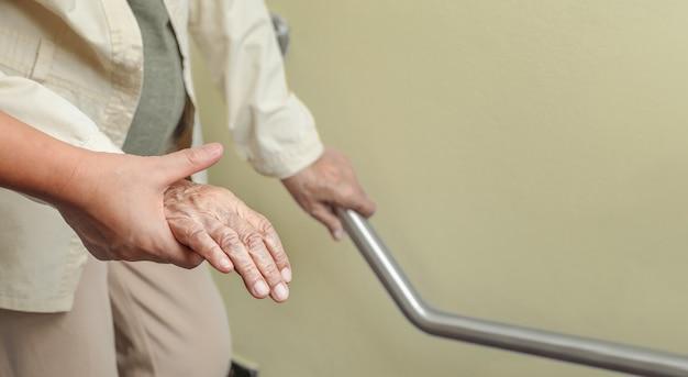 Mulher idosa segurando no corrimão com cuidador