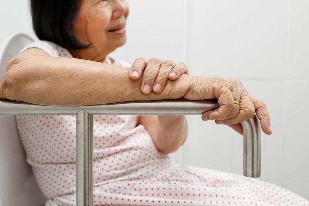 Mulher idosa segurando no corrimão no banheiro.
