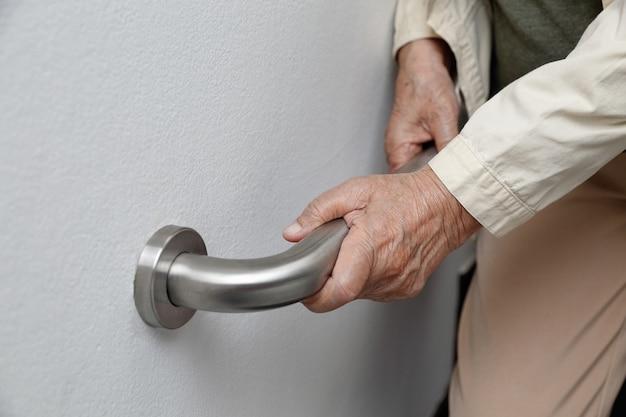 Mulher idosa segurando no corrimão para passos de segurança