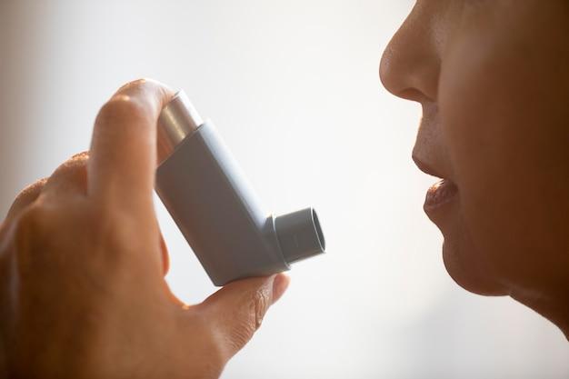 Mulher idosa segurando um inalador para asma