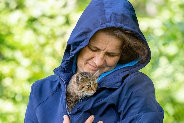 Mulher idosa segurando um pequeno gatinho listrado, um gatinho nos braços de uma mulher