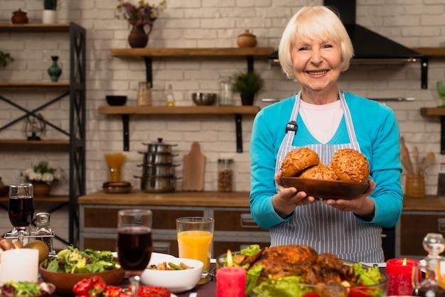 Mulher idosa segurando um prato com pão e olhando para a câmera