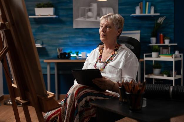 Mulher idosa segurando um tablet em busca de inspiração
