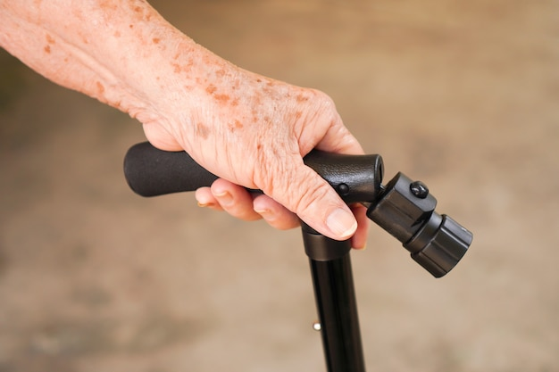 Mulher idosa segurando uma bengala ou bengala