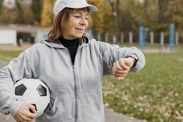Mulher idosa segurando uma bola de futebol e olhando para o relógio ao ar livre