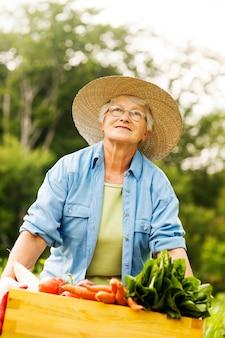 Mulher idosa segurando uma caixa com vegetais
