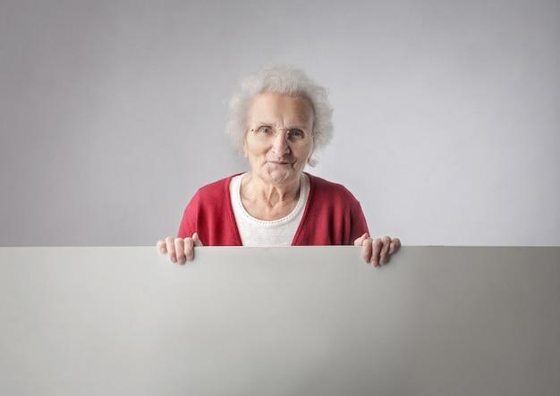 Mulher idosa, segurando uma placa