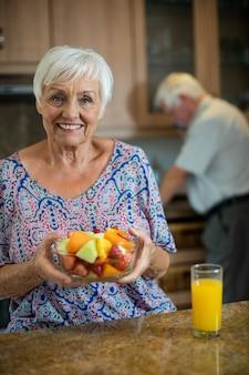 Mulher idosa segurando uma tigela de frutas enquanto um homem trabalha na cozinha de casa