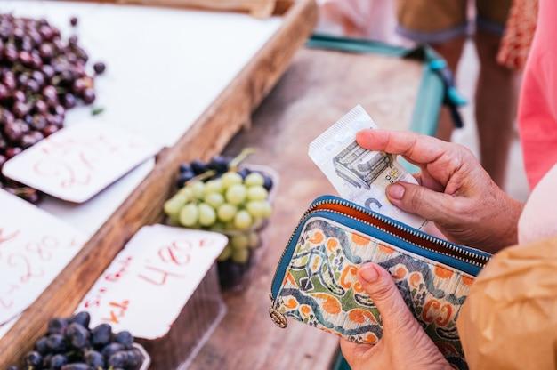 Mulher idosa sem saber tirando uma nota de 5 euros da carteira para pagar