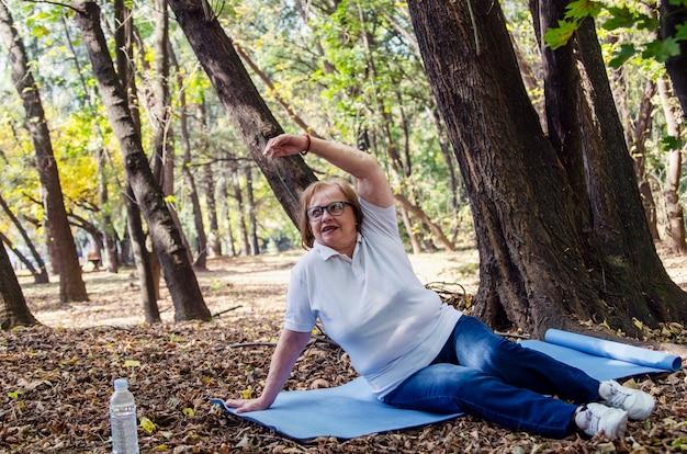 Mulher idosa sênior, estendendo-se no tapete de ioga ao ar livre em madeira. cabelo cinza amadureceu treino feminino ao ar livre para perder excesso de peso