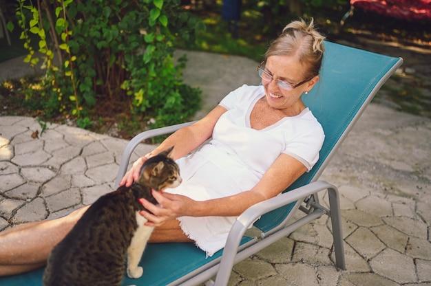 Mulher idosa sênior feliz sorridente em copos relaxando no jardim de verão ao ar livre, abraçando o gato malhado doméstico. conceito de animais de estimação idosos aposentados