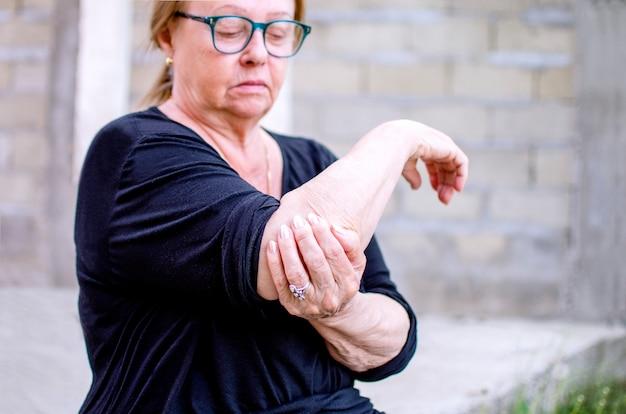 Mulher idosa sênior, massageando o cotovelo e o braço que sofrem de dor de reumatismo. senhora idosa com artrite no osso da mão