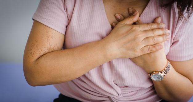 Mulher idosa sênior não identificada, sentada na cama, sofrendo de ataque cardíaco súbito e segurar o peito. conceito de cuidados de saúde de emergência e afetados pela ressuscitação cardiopulmonar, problema cardíaco.
