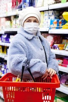 Mulher idosa sênior que faz compras no supermercado seleciona produtos em uma máscara médica. coronavírus pandêmico covid 19