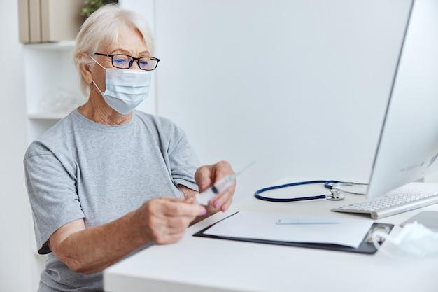 Mulher idosa sentada à mesa com uma seringa no hospital de vacinação de mãos