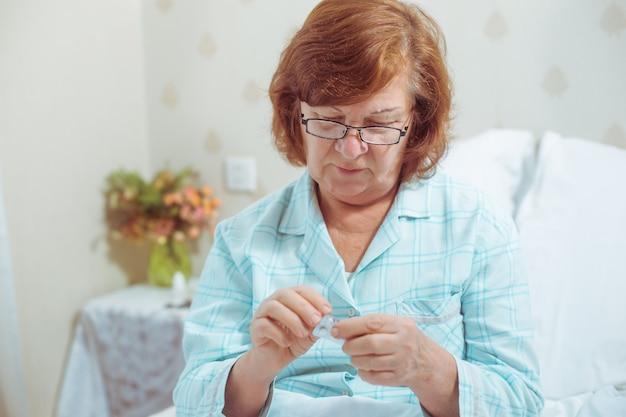 Mulher idosa sentada de vidro, sentada na cama em casa, tomando comprimidos avó ruiva, doente, caucasiana