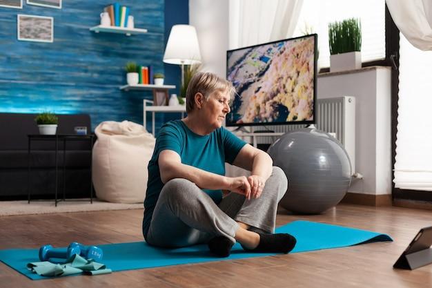 Mulher idosa sentada em posição de lótus no tapete de ioga, treinando os músculos do corpo e reduzindo o peso