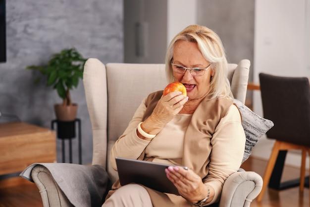 Mulher idosa sentada em uma cadeira em casa durante o bloqueio, usando um tablet e comendo maçã