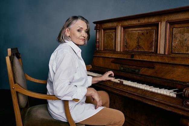 Mulher idosa sentada em uma cadeira perto da apresentação de música de piano