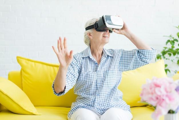 Mulher idosa sentada no sofá amarelo, apreciando os óculos de realidade virtual
