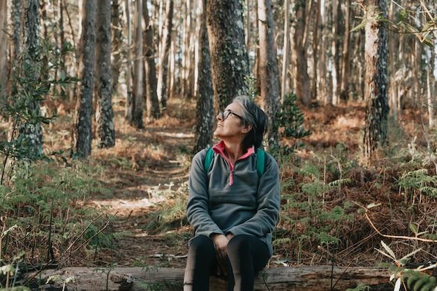 Mulher idosa sentada sobre um tronco na floresta durante um dia outonal com espaço de cópia