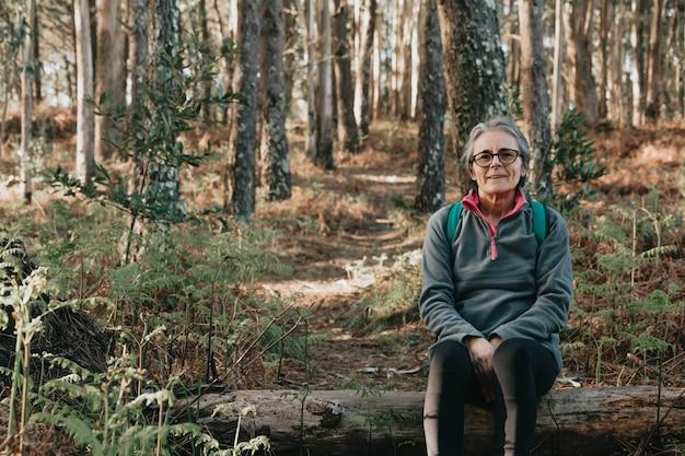 Mulher idosa sentada sobre um tronco sorrindo na floresta durante um dia outonal com espaço de cópia