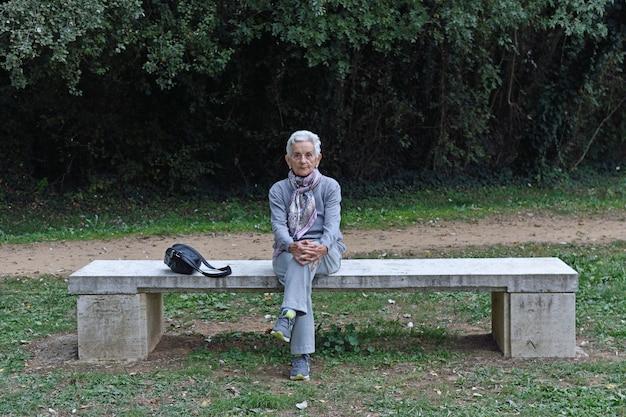 Mulher idosa sentada sozinha em um banco em um parque