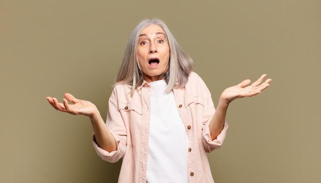 Mulher idosa sentindo-se extremamente chocada e surpresa, ansiosa e em pânico, com um olhar estressado e horrorizado
