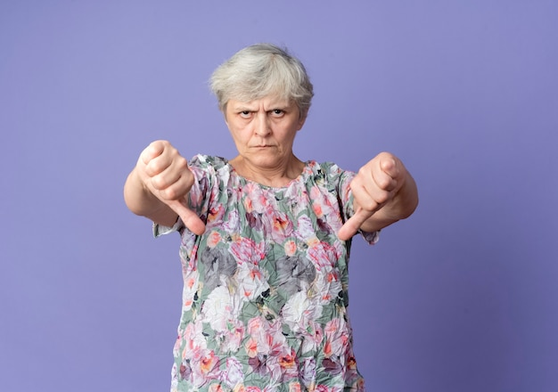 Mulher idosa séria com o polegar para baixo com as duas mãos isoladas na parede roxa