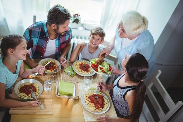 Mulher idosa servindo refeição para sua família